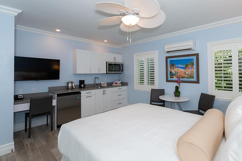 Studio Room with Queen Bed, Kitchenette, and dining table and two chairs.