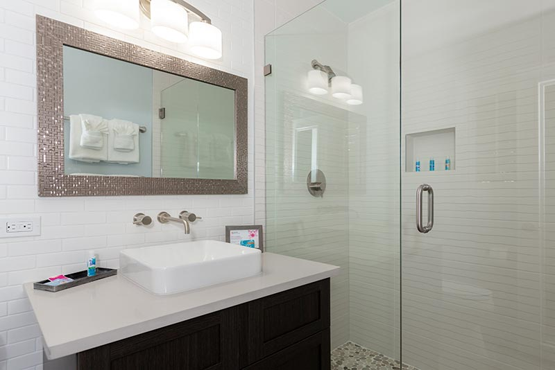 Bathroom sink with mirror and shower.